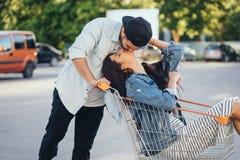 Hübscher Kerl trägt seine Freundin im Wagen Kerl küsst seine Freundin stockfoto