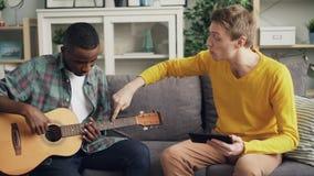 Hübscher Kerl unterrichtet seinen Afroamerikanerfreund, die Gitarre unter Verwendung der Tablette, Männer zu spielen sitzen auf d stock video