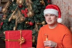 Hübscher Kerl in Weihnachtsmann-Hut hält ein Glas Champagner sitzend unter dem Baum, der durch Kästen Geschenke umgeben wird Weih lizenzfreies stockbild