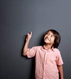 Hübscher kleiner Junge, der aufwärts zeigt und schaut Lizenzfreies Stockfoto
