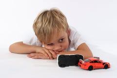Hübscher kleiner Junge, der hinter zerschmetterten Autospielwaren liegt und gebohrt oder müde scheint lizenzfreie stockfotografie