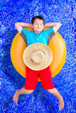 Hübscher kleiner Junge, der weg im Pool döst Stockfotografie