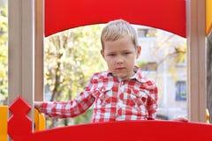 Hübscher kleiner Junge im Hemd steht auf Spielplatz Lizenzfreies Stockfoto