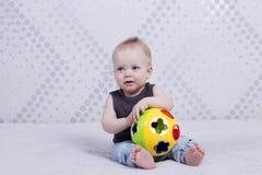 Hübscher kleiner Junge mit einem tou Ball, der wie ein Trainer aussieht Stockfotografie