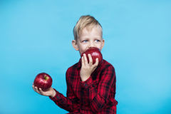 Hübscher kleiner Junge mit zwei roten Äpfeln Studioporträt über blauem Hintergrund lizenzfreies stockbild