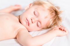 Hübscher Kleinkindjunge mit dem blonden Haar schlafend auf weißem Schlechtem Stockbild