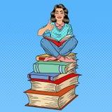 Hübscher Knall Art Young Woman Sitting auf dem Stapel von Büchern und von Lesebuch mit dem Handzeichen-Daumen oben Lizenzfreie Stockfotos