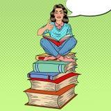 Hübscher Knall Art Young Woman Sitting auf dem Stapel von Büchern und von Lesebuch mit dem Handzeichen-Daumen oben Stockfotos