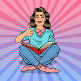 Hübscher Knall Art Young Woman Sitting und Lesebuch mit dem Handzeichen-Daumen oben Stockbild