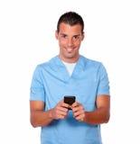 Hübscher Krankenschwestermann, der mit seinem Mobiltelefon simst Lizenzfreies Stockfoto