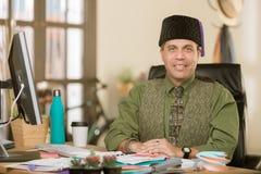 Hübscher kreativer Geschäftsmann in einem Büro, das ein Fez trägt stockfoto