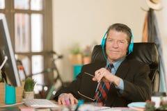 Hübscher kreativer Geschäftsmann in einer Klage hörend auf Kopfhörer lizenzfreies stockbild