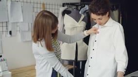 Hübscher Kunde versucht auf hergestelltem Hemd und teilt ihre Meinung, während Kleidungsdesigner misst und überprüft stock video footage