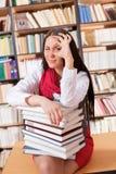 Hübscher Kursteilnehmer mit den Büchern, die okayzeichen zeigen lizenzfreie stockbilder