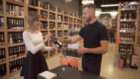 Hübscher kurzhaariger Mädchenverkäufer bietet Wein dem Besucher an Männlicher Kunde nimmt eine Flasche Wein angeboten vom Verkäuf stock footage