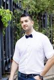 Hübscher lächelnder bärtiger Mann mit weißem Hemd und Fliege auf der Straße Lizenzfreies Stockbild