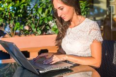 Hübscher lächelnder Blogger, der Laptop-Computer verwendet, um Blogs beim Sitzen Café am im Freien am sonnigen Tag zu schreiben Stockbilder