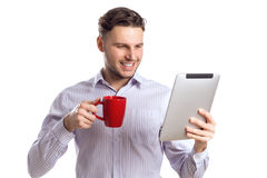 Hübscher lächelnder Geschäftsmann Holding Red Cup und liest Computer Stockfotos