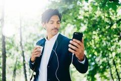 Hübscher lächelnder Geschäftsmann unter Verwendung des Smartphone für listining Musik beim Gehen in Stadtpark Junger Mann, der se Lizenzfreie Stockfotografie