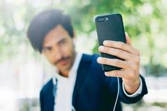 Hübscher lächelnder Geschäftsmann unter Verwendung des Smartphone für listining Musik beim Gehen in Stadtpark Junger Mann, der se Stockfotografie
