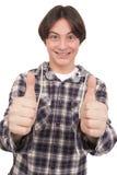 Hübscher lächelnder Jugendlicher, der sich Daumen zeigt Lizenzfreies Stockfoto
