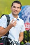 Hübscher lächelnder junger männlicher Golfspieler hält Ball stockfoto