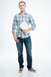 Hübscher lächelnder junger Mann, der Laptop steht und hält Stockfotos
