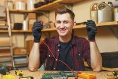 Hübscher lächelnder junger Mann, der in der Zimmereiwerkstatt am Holztischplatz mit Stück Holz arbeitet stockfotos