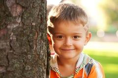 Hübscher lächelnder kleiner Junge nahe einem Baum. Stockfoto
