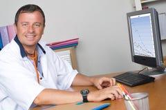 Hübscher lächelnder männlicher Doktor, der an Computer am Schreibtisch arbeitet Lizenzfreie Stockfotos