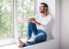 Hübscher lächelnder Mann, der auf Fensterbrett sich entspannt stockfoto