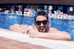 Hübscher lächelnder Mann, der im Swimmingpool mit kaltem Getränk sich entspannt Stockfotografie