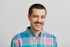 Hübscher lächelnder Mann, der in der Kamera steht und schaut Lokalisiert auf weißer Wand Stockfotografie