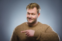 Hübscher lächelnder Mann des Porträts, der Finger auf die Seite lokalisiert auf Grau zeigt Lizenzfreies Stockfoto
