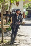 Hübscher lächelnder Mann kleidete alle im schwarzen Leder mit Klinge und Hut und Feder und die Stiefel, die Baum beim Oklahoma Re lizenzfreies stockbild