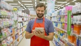 Hübscher lächelnder Supermarktangestellter mit Bart unter Verwendung der digitalen Tablette, die unter Regalen im Supermarkt steh stock video