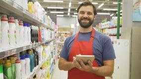 Hübscher lächelnder Supermarktangestellter mit der PC-Tablette, die unter Regalen steht stock video
