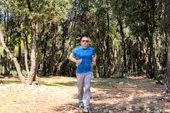 Hübscher Läufergeländelauf des jungen Mannes auf Spur im männlichen Training des Sommerwaldjungen Athleten lizenzfreie stockbilder