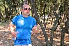 Hübscher Läufergeländelauf des jungen Mannes auf Spur im männlichen Training des Sommerwaldjungen Athleten stockbild