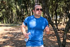 Hübscher Läufergeländelauf des jungen Mannes auf Spur im männlichen Training des Sommerwaldjungen Athleten lizenzfreies stockfoto