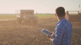 Hübscher Landwirt mit der Tablette, die mit Mähdrescher im Hintergrund steht Technologie-Notentablette des Landwirtgebrauches mod stock footage