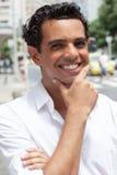 Hübscher lateinischer Kerl mit einem toothy Lächeln in der Stadt Lizenzfreie Stockfotos