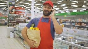 Hübscher Lebensmittelgeschäftlieferer, der mit Mobile spricht und Schrenzpapiertasche hält stock video