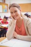 Hübscher Lehrer, der in der Hand an der Kamera mit Kopf lächelt lizenzfreies stockfoto