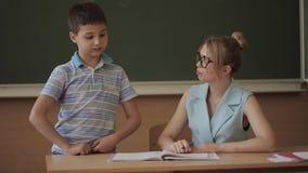 Hübscher Lehrer im Klassenzimmer, das am Schreibtisch sitzt und Kinder fragt Ausbildung, Volksschule, Lernen und Leute stock footage