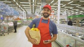 Hübscher Lieferer in der roten Uniform mit der Papiertüte, die im Supermarkt steht, lächelt er an der Kamera stock video