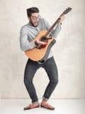 Hübscher lustiger Mann, der eine Akustikgitarre gegen Schmutzwand spielt Stockbild
