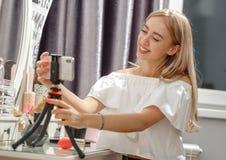 Hübscher Mädchen Blogger stellt das Telefon auf dem Stand auf der Frisierkommode für schießendes Video für ihr Blog ein stockbild