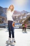 Hübscher Mädcheneislauf im Freien an der Eisbahn stockbild
