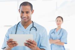 Hübscher männlicher Doktor, der digitale Tablette hält Stockbild